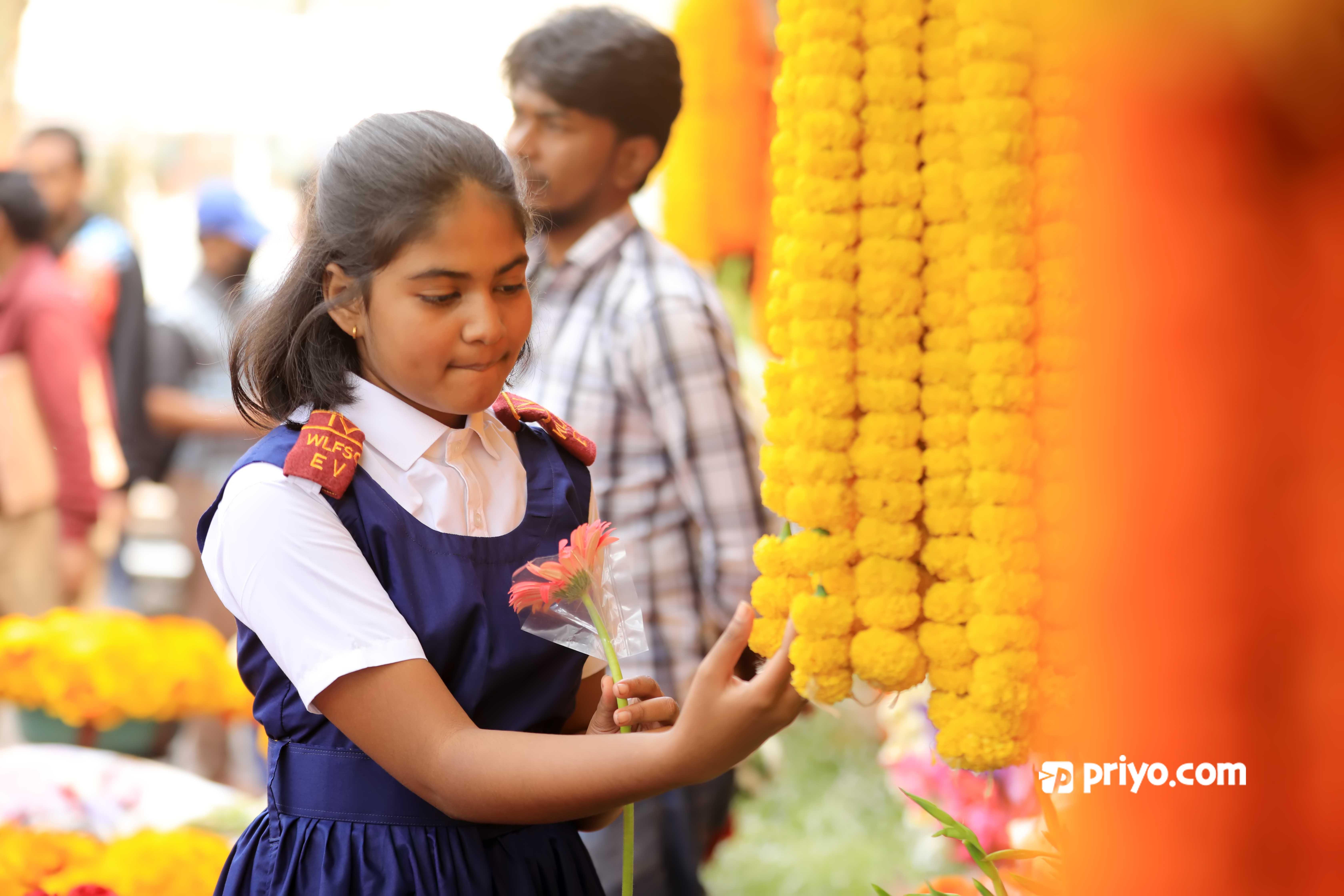 ঢাকার শাহবাগে ফুলের বাজারে সোমবার ফুল কিনছে এক স্কুলছাএী ।  ছবি : শামছুল হক রিপন