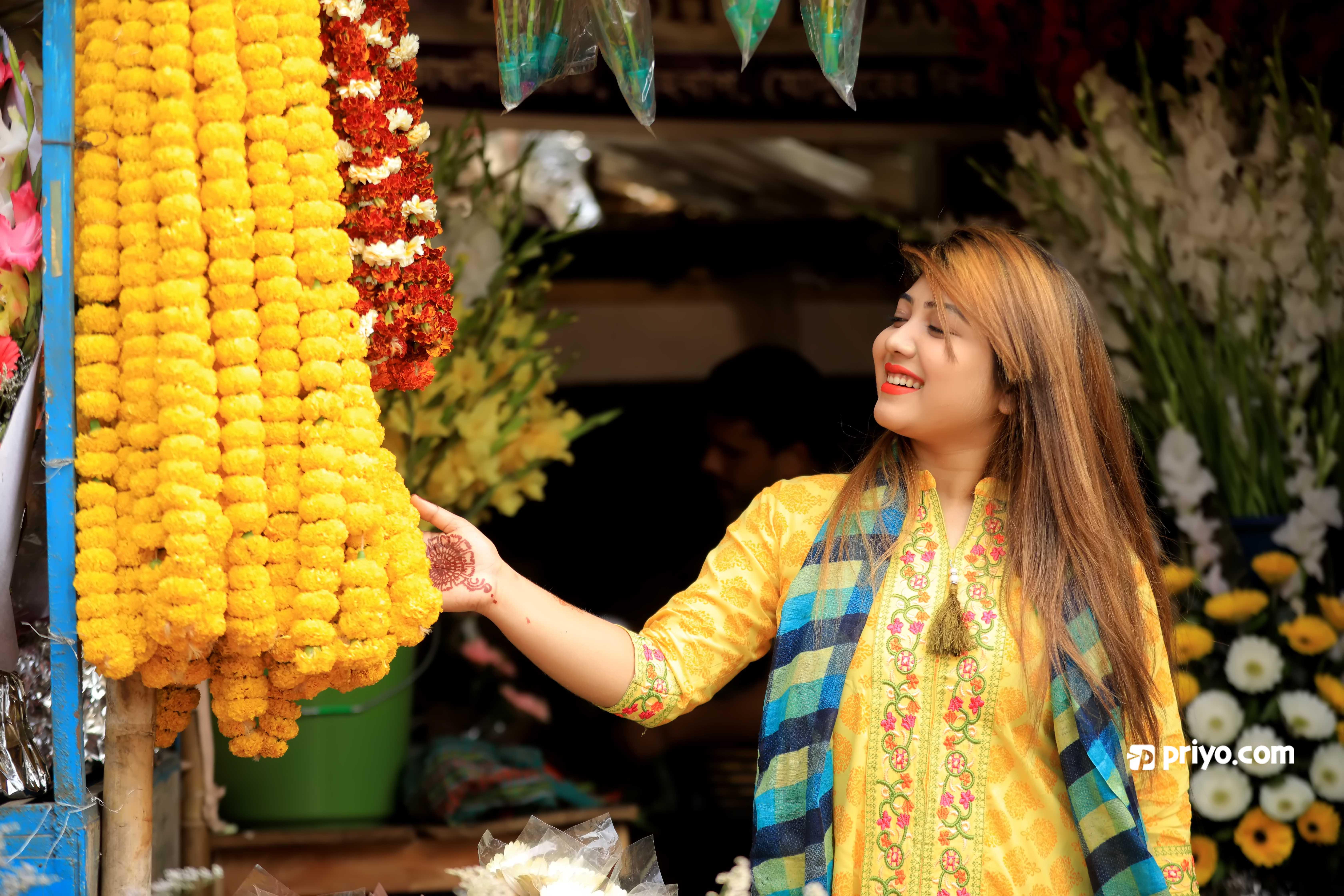 ঢাকার শাহবাগে ফুলের বাজারে ফুল কিনছেন এক তরুণী।  ছবি: শামছুল হক রিপন